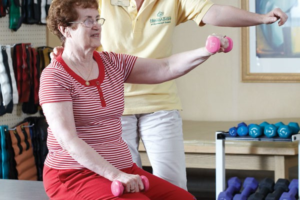 Physical therapist and resident work by lifting weights