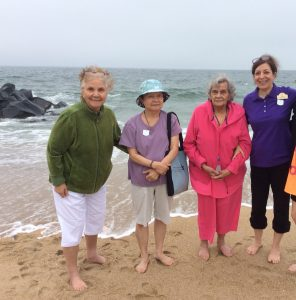 Three Seniors and Care Manager On Beach