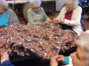 Group of Seniors Making Fleece Blanket