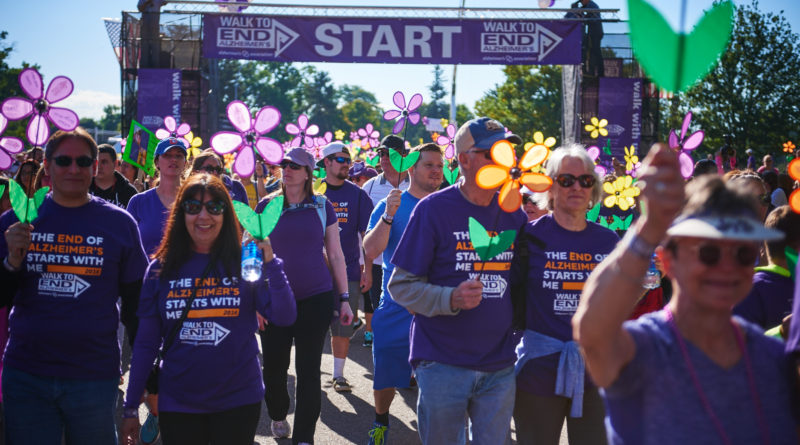 People Walking in Alzheimer's Awareness Shirts and Holding Flowers