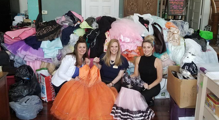 Three ladies donate a mountain of dresses for a prom dress drive