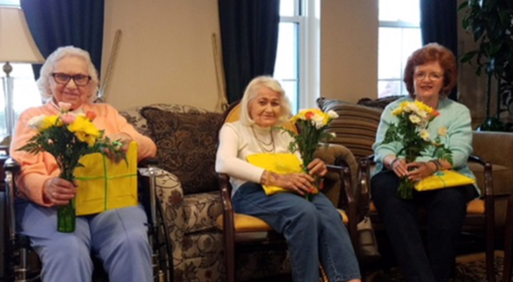 Three residents sitting down holding bouquet of flowers