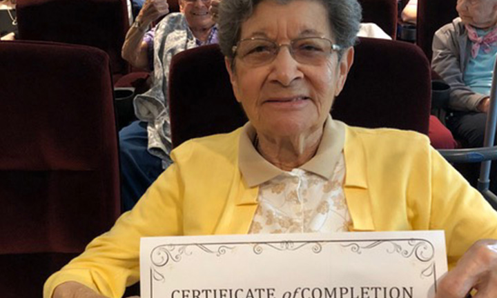 Older Female Holding Graduation Certificate