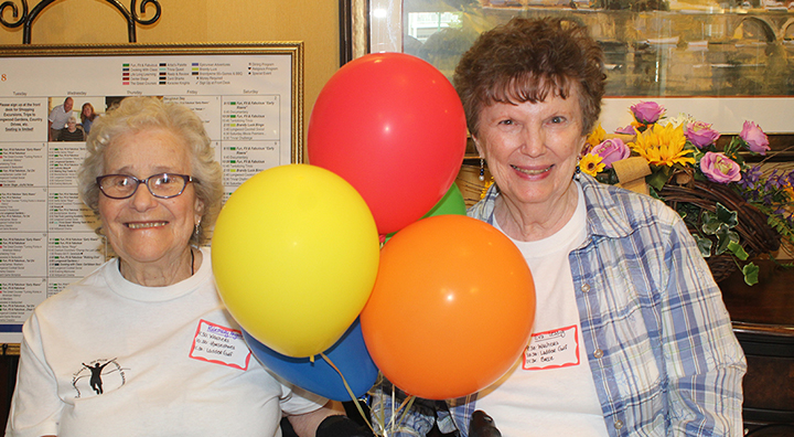 Two Female Competitors Pose with Balloons