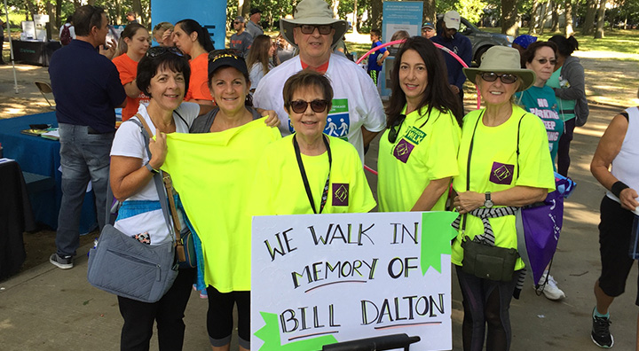 "Judy Dalton Holds Sign ""We Walk in Memory of  Bill Dalton"""