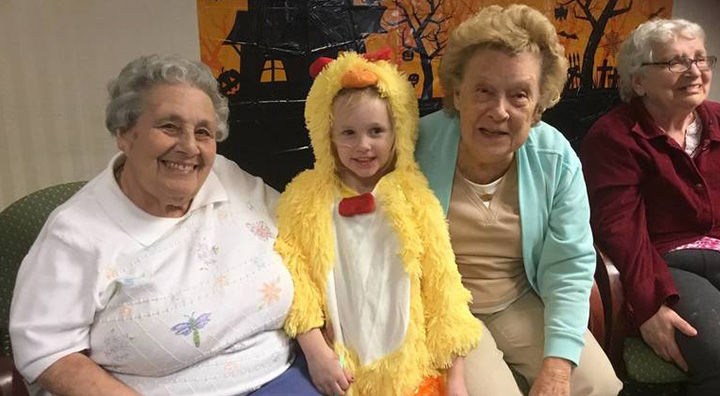 Two Seniors Pose with Child in Costume