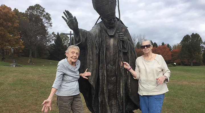 Two Princeton Residents Pose with Pope Statue on All Saints Day