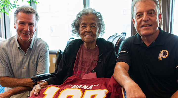 Carletha West Accepts Red Skins Jersey for her 107th Birthday from Redskins president Bruce Allen