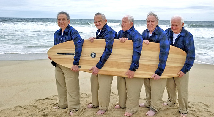 "Princeton Seniors Hold a Surf Board at Sea Grit Beach in honor of ""Surfer Girl"" release"