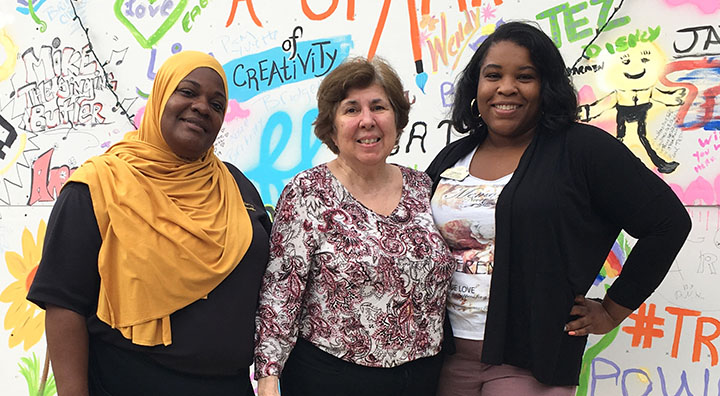 Brandywine Living at Moorestown Resident and Two Team Members Pose with Graffiti Wall