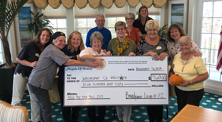 Brandywine Living Holds a Large Check for the Worcester County Warriors