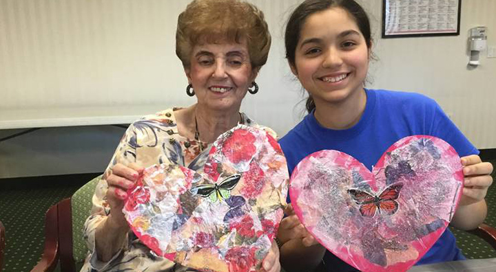 Female Brandywine Resident and Ying Hua Student Hold Valentine Hearts