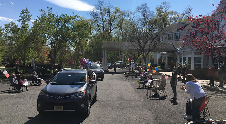 Residents Wave to Family and Friends During A Car Parade