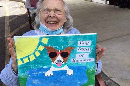 Senior Female Holds Dog Themed Artwork
